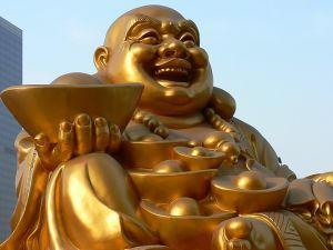 Statue monumentale d'un bouddha rieur portant les attributs de la richesse